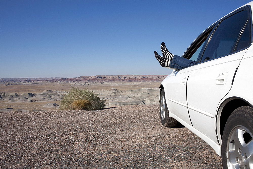 USA, Arizona, Winslow, Woman sticking feet out of car window parked in desert