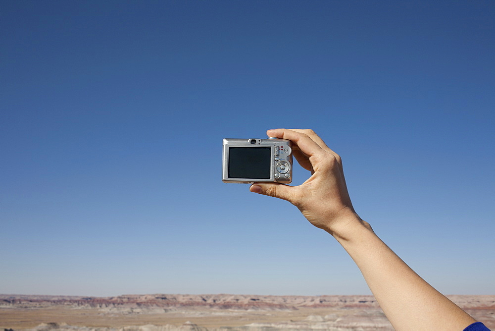 Hand of woman holding camera up against blue sky