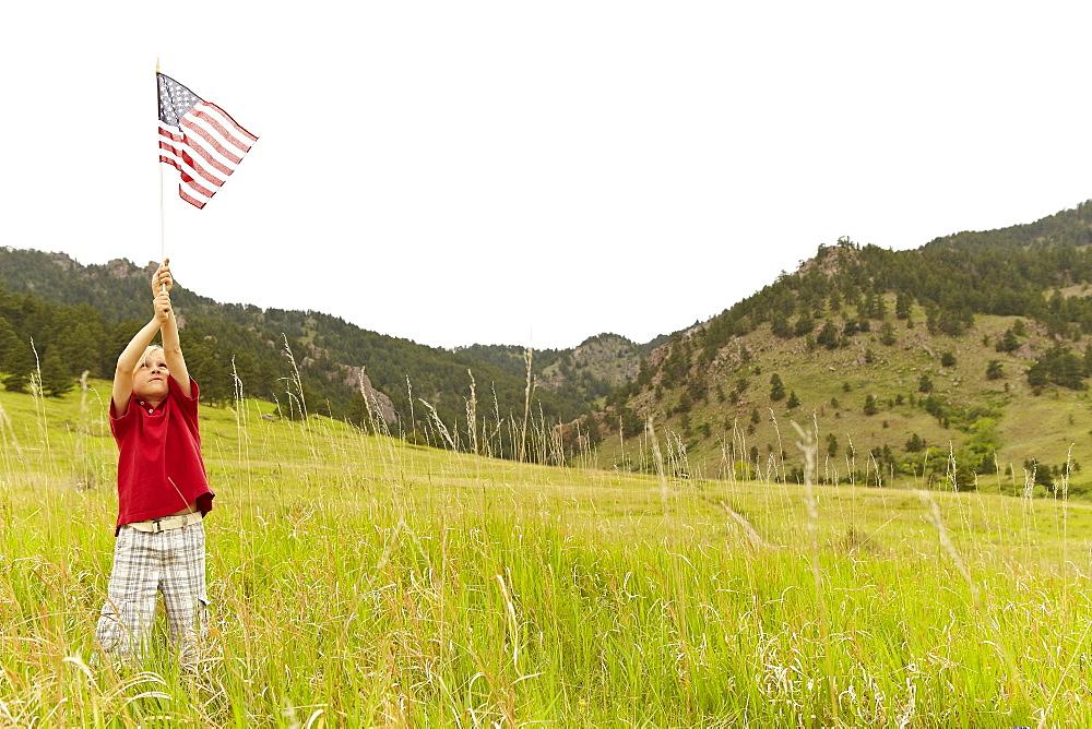 Boy (6-7) waving American flag in meadow