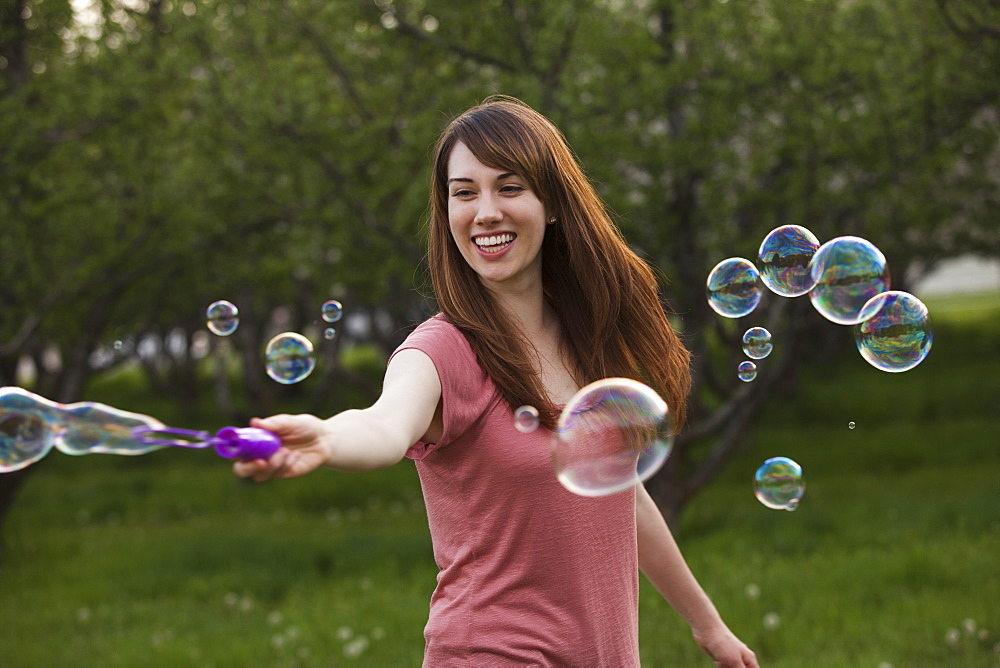Young woman blowing bubbles in orchard