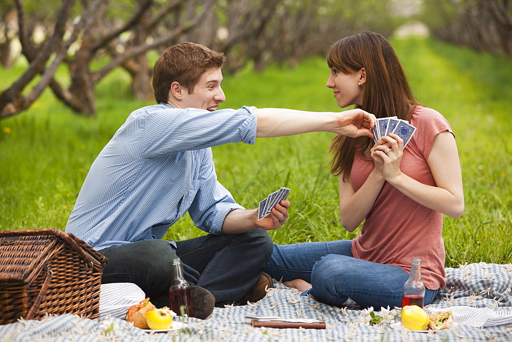 USA, Utah, Provo, Young couple playing cards during picnic in orchard