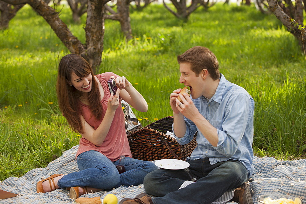 USA, Utah, Provo, Young couple having picnic in orchard