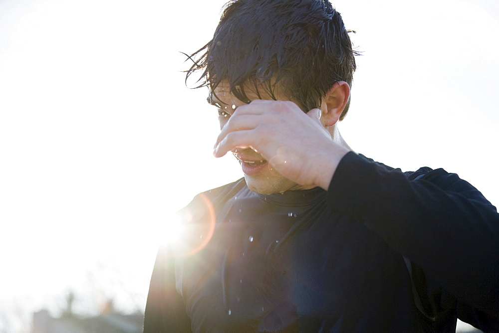 Man in sports clothing back lit by sun