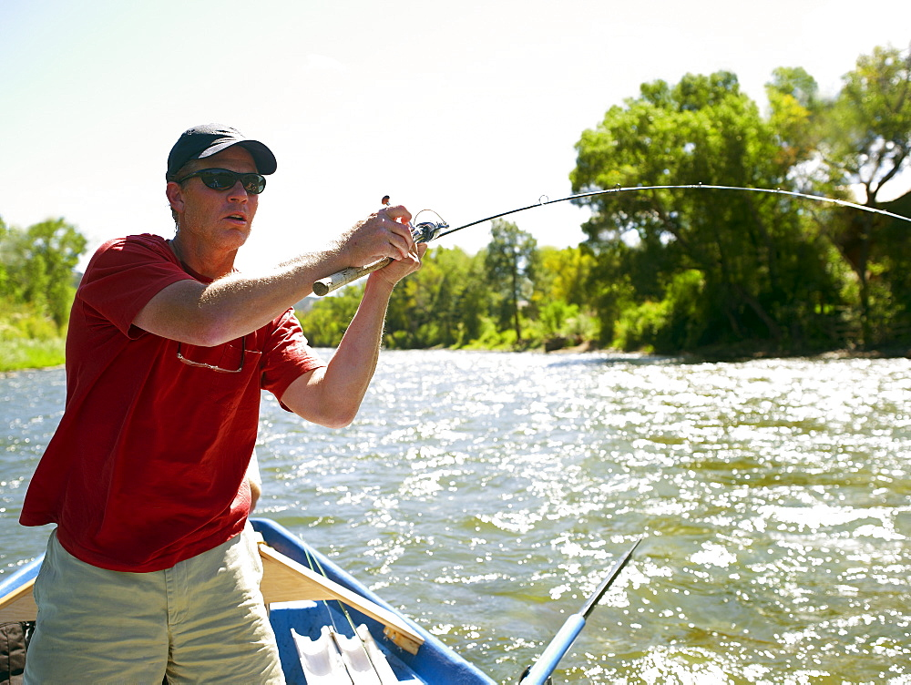 USA, Colorado, Man fly-fishing from boat