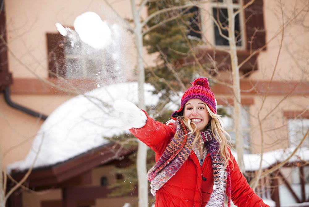 USA, Utah, Salt Lake City, Portrait of young woman throwing snowball