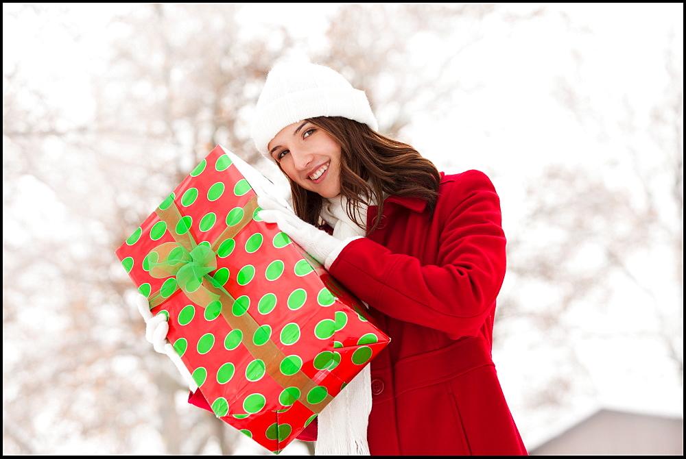 USA, Utah, Lehi, Portrait of young woman holding Christmas gift outdoors