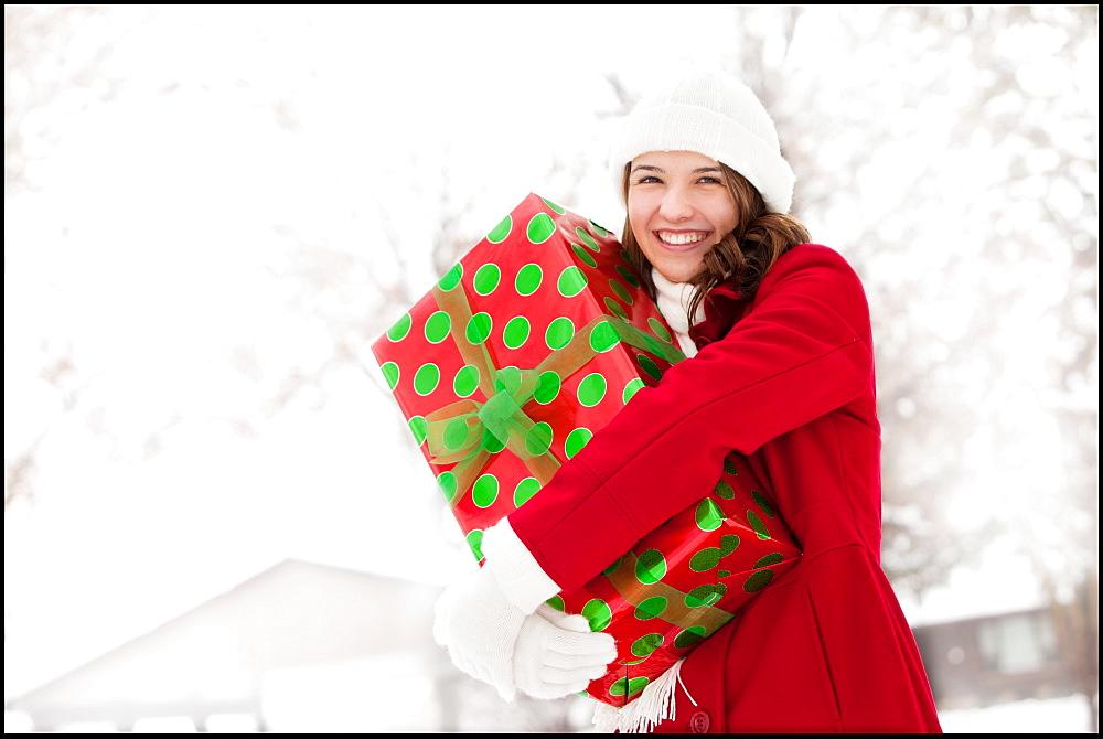 USA, Utah, Lehi, Portrait of young woman hugging Christmas gift outdoors