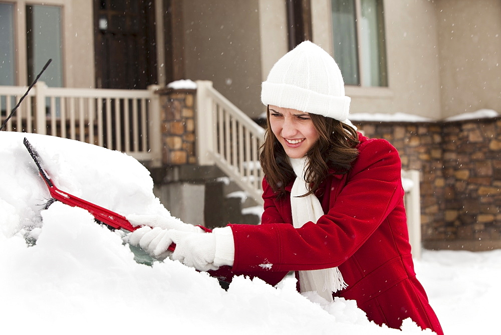 USA, Utah, Lehi, Young woman scraping snow from car