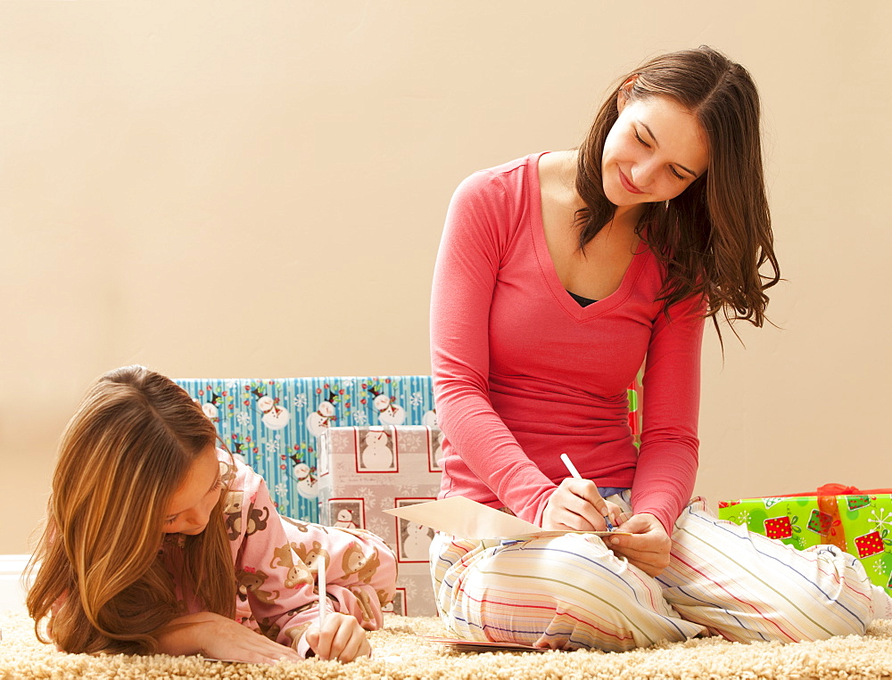 Two sisters (6-7, 18-19) wrapping Christmas presents