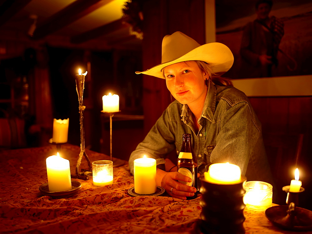 USA, Colorado, Portrait of cowgirl sitting at table with candles