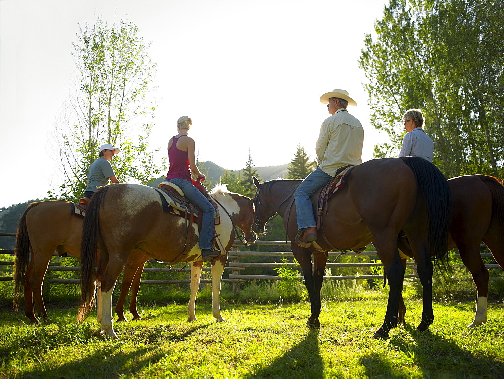 USA, Colorado, Family with teenage boy (14-15) riding horses on ranch