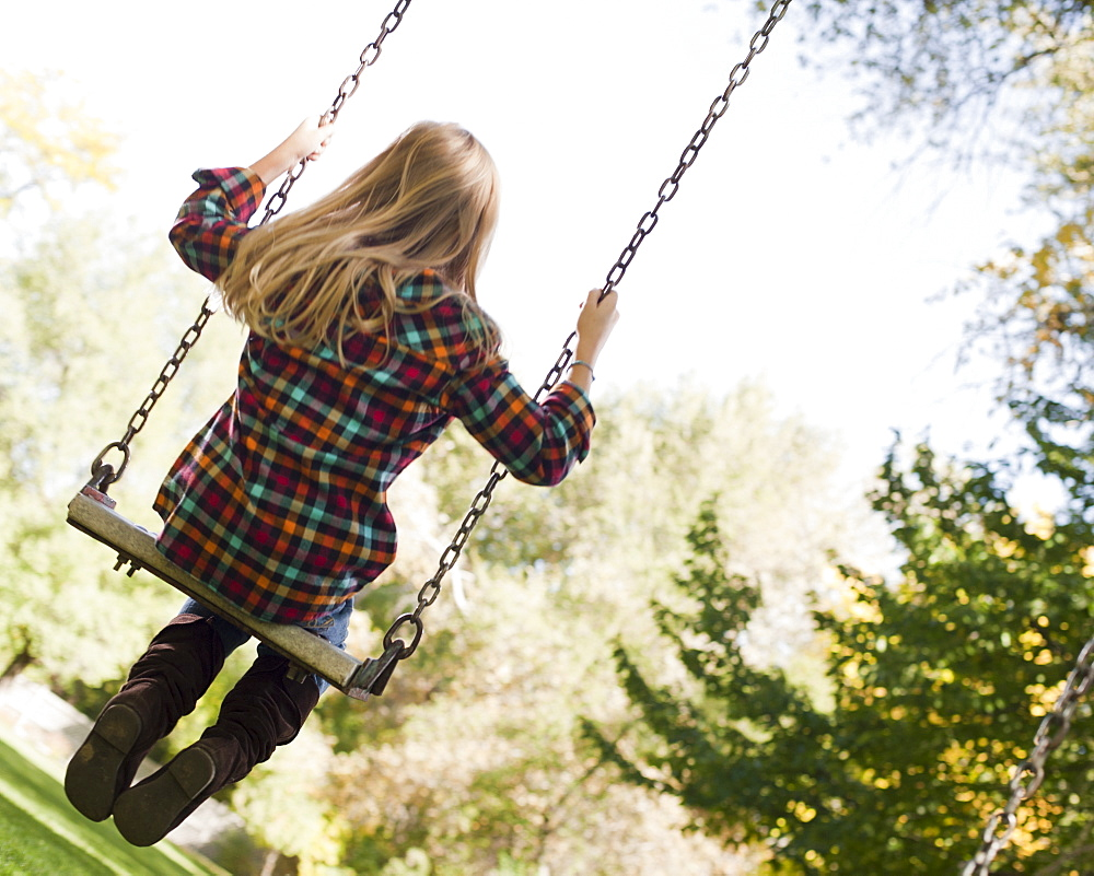 USA, Utah, girl  (6-7) swinging on tree swing