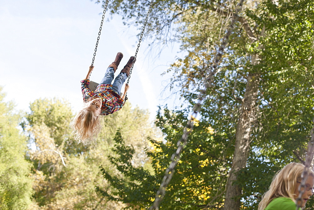 USA, Utah, girl  (6-7)swinging on tree swing