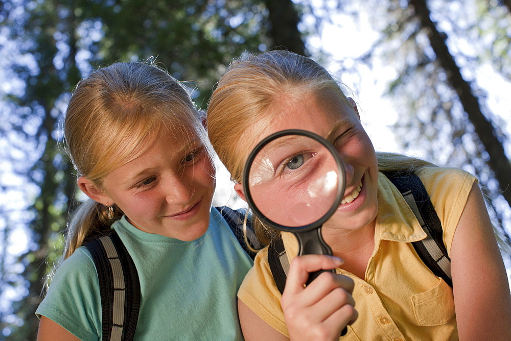 Canada, British Columbia, Fernie, sisters looking through magnifying glass