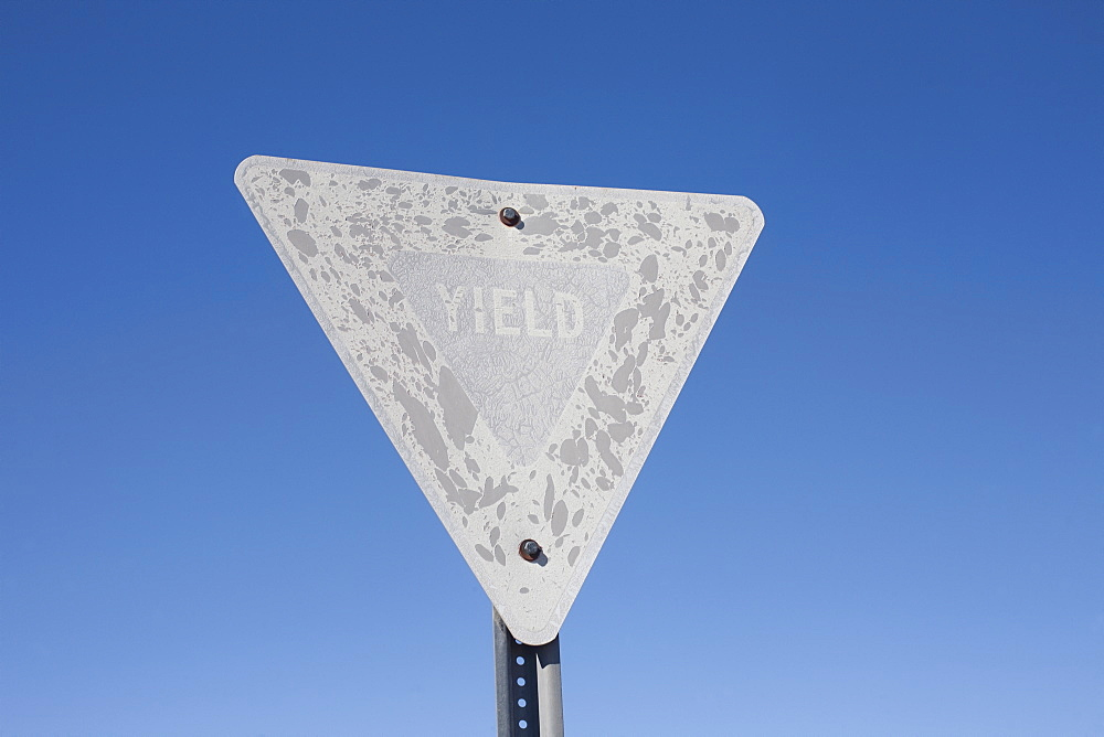 USA, Arizona, Winslow, Old yield sign against blue sky