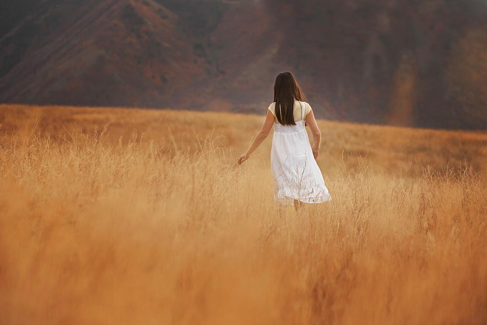 Girl (10-11) walking in wheat field