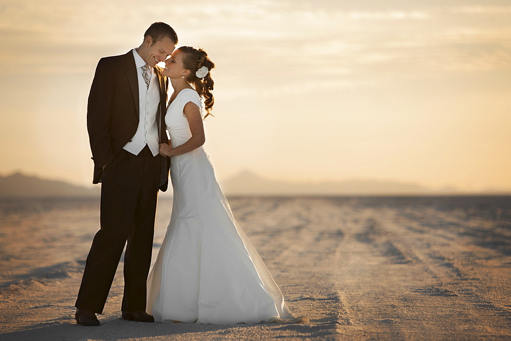 Bride and groom embracing in desert