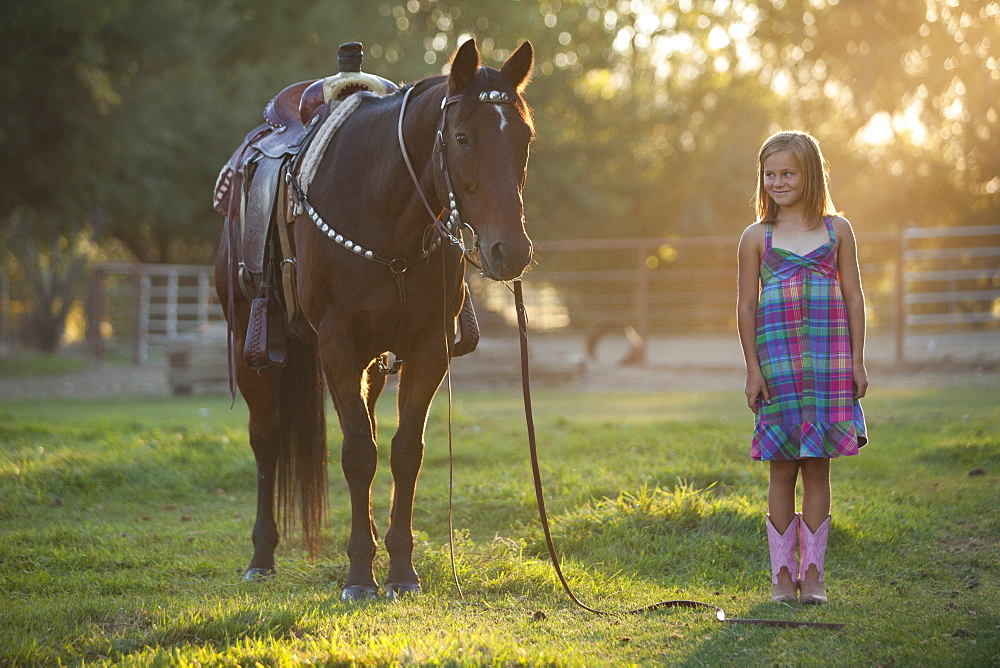 Girl (8-9) standing with horse in paddock