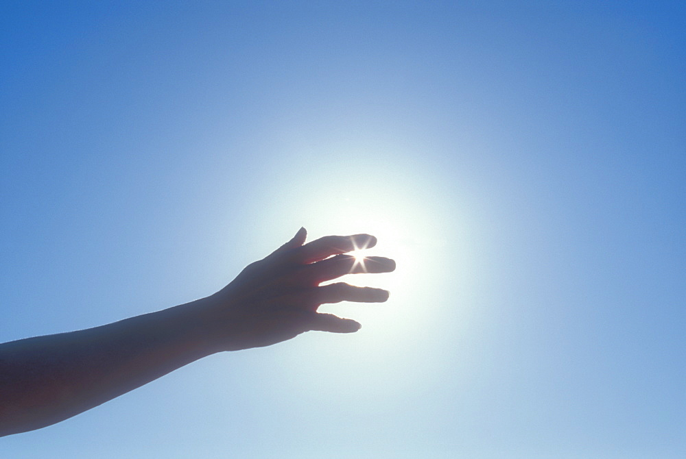 Silhouette of woman's hand against sky