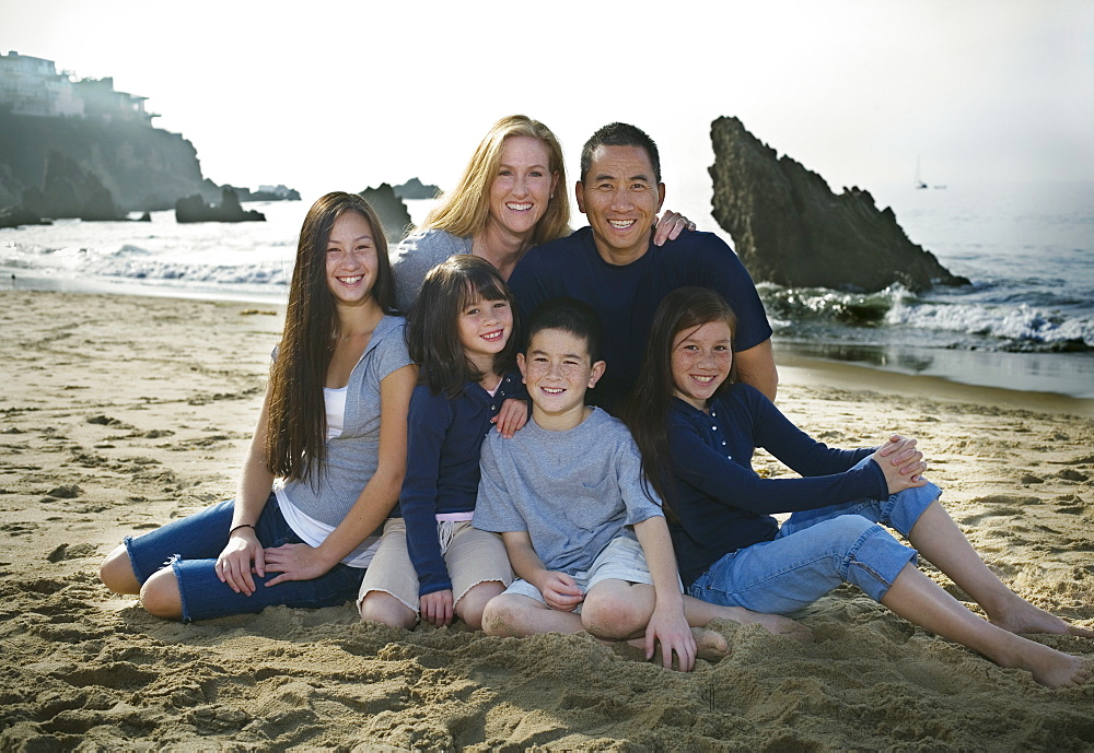 Family sitting together at the beach