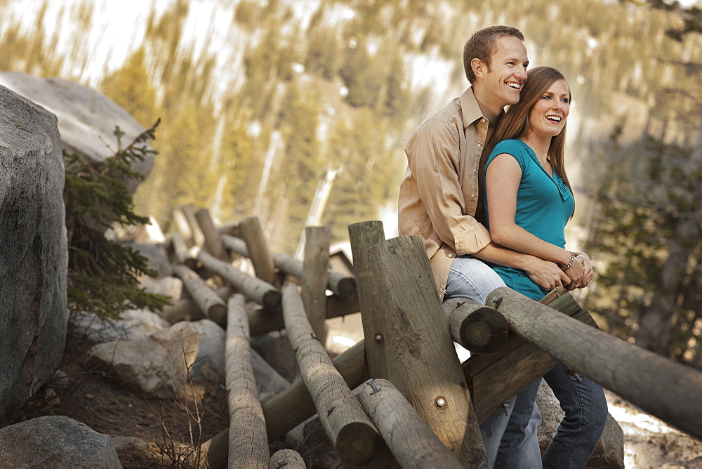 Happy couple sitting on log fence