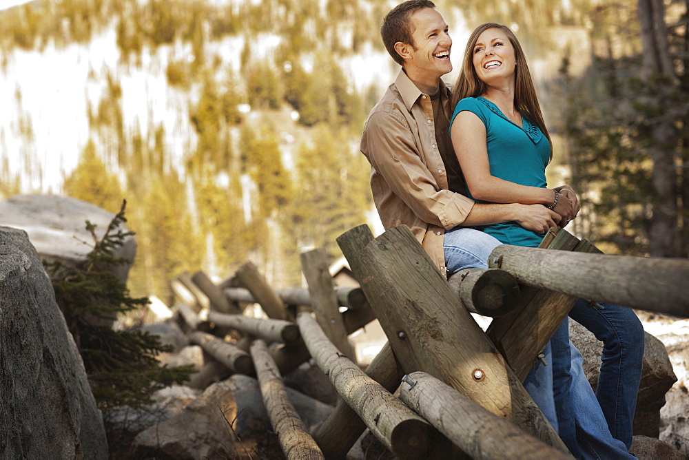 Laughing couple sitting on log fence