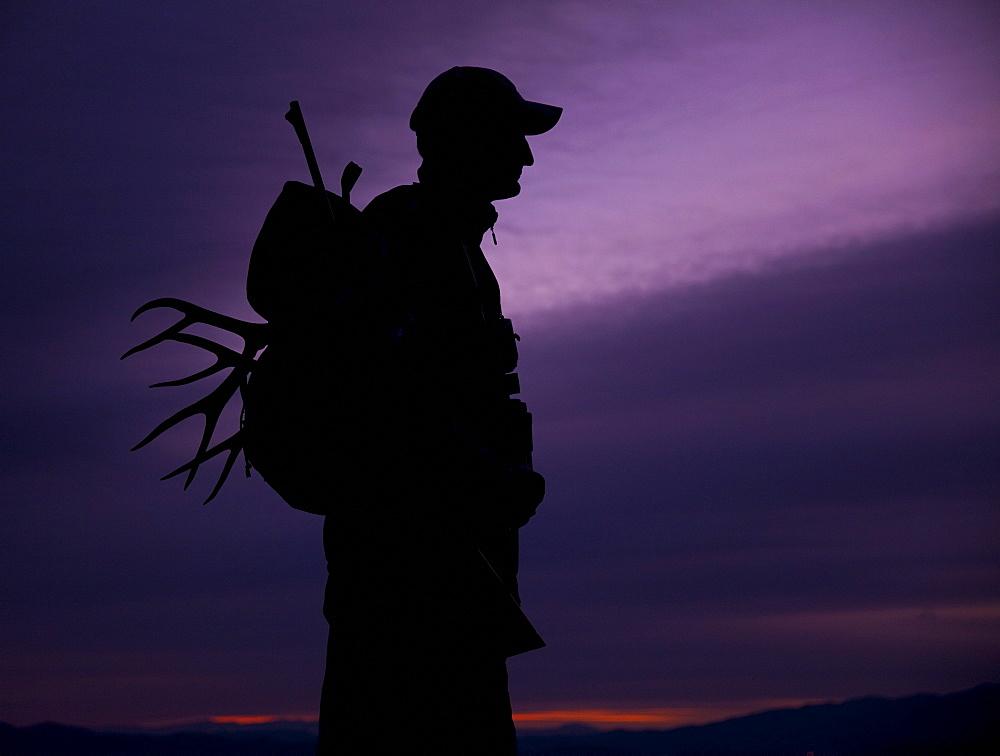 Hunter with deer antler in his backpack