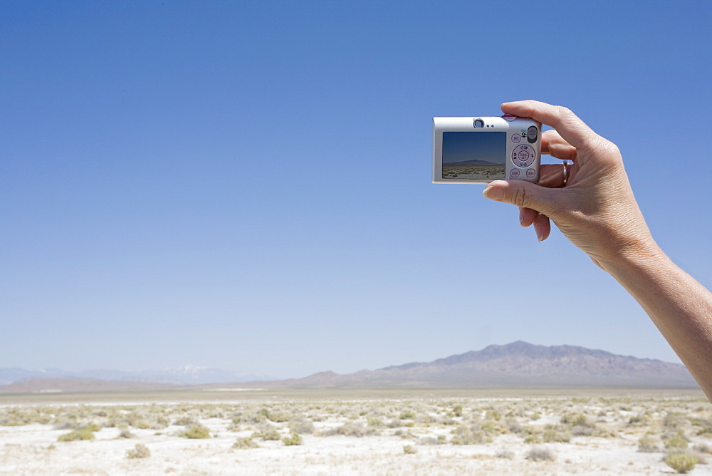 Hand holding a camera in the desert