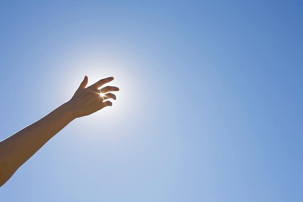 Hand in front of a sun flare in the sky