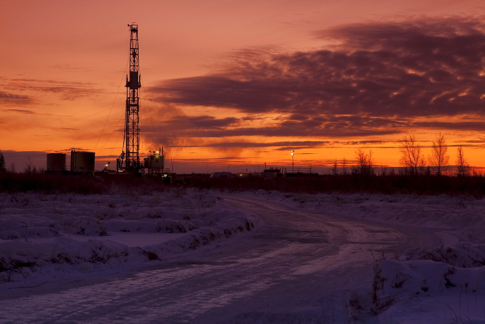 Snowy road at dusk with oil drilling rig in background