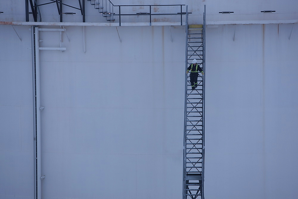 Worker walking down stairs on an oil tank