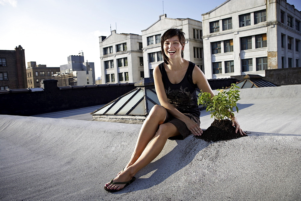 Woman sitting on rooftop beside aspen sapling