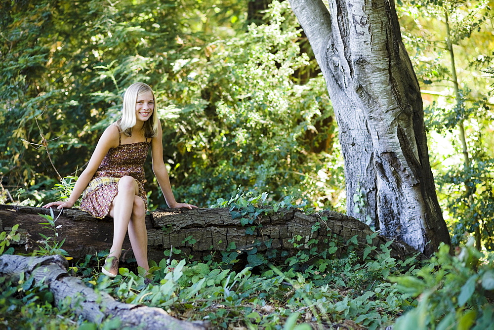Young woman sitting on log