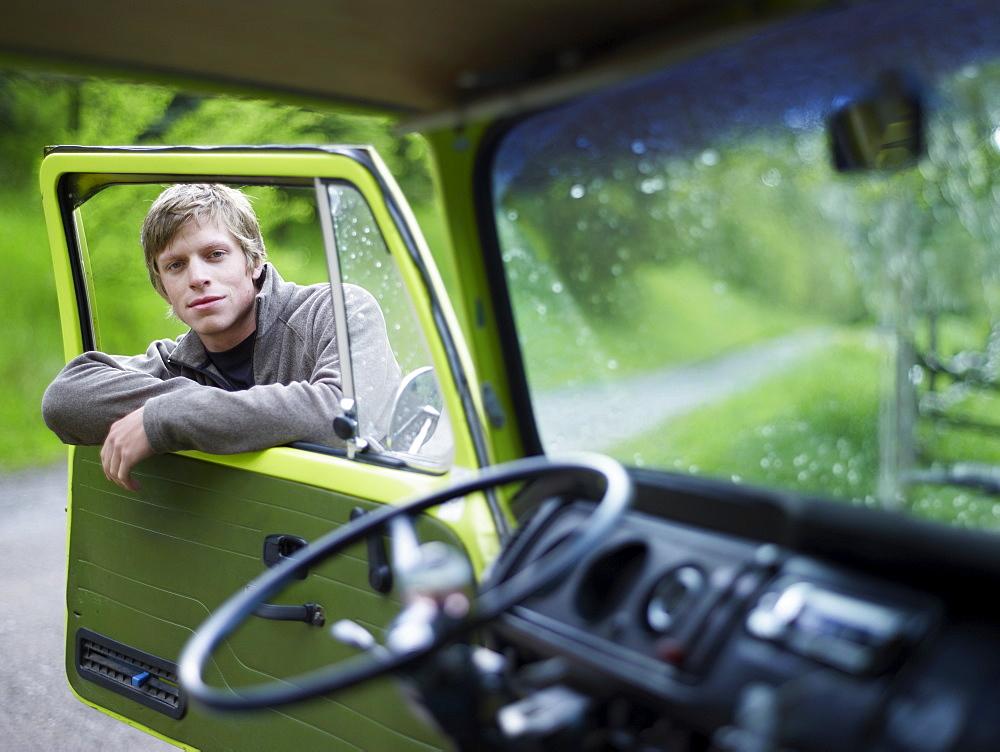 Young man hanging on door