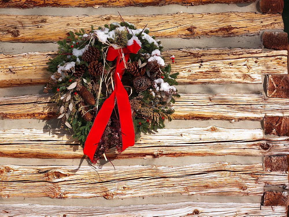 A Christmas wreath on a cabin wall