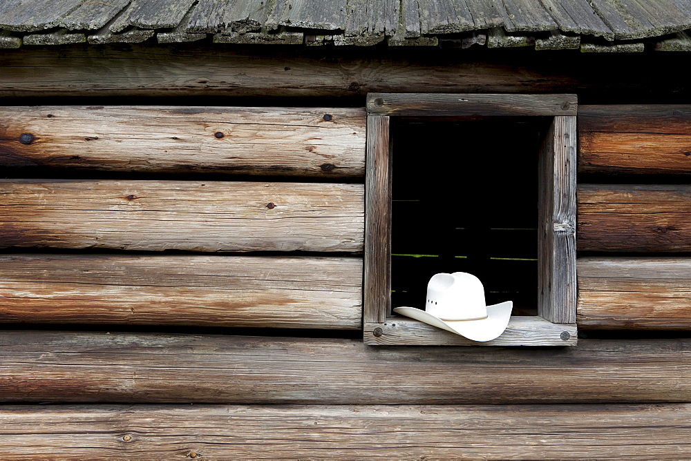 A cowboy hat in the window of a cabin - 1178-6401