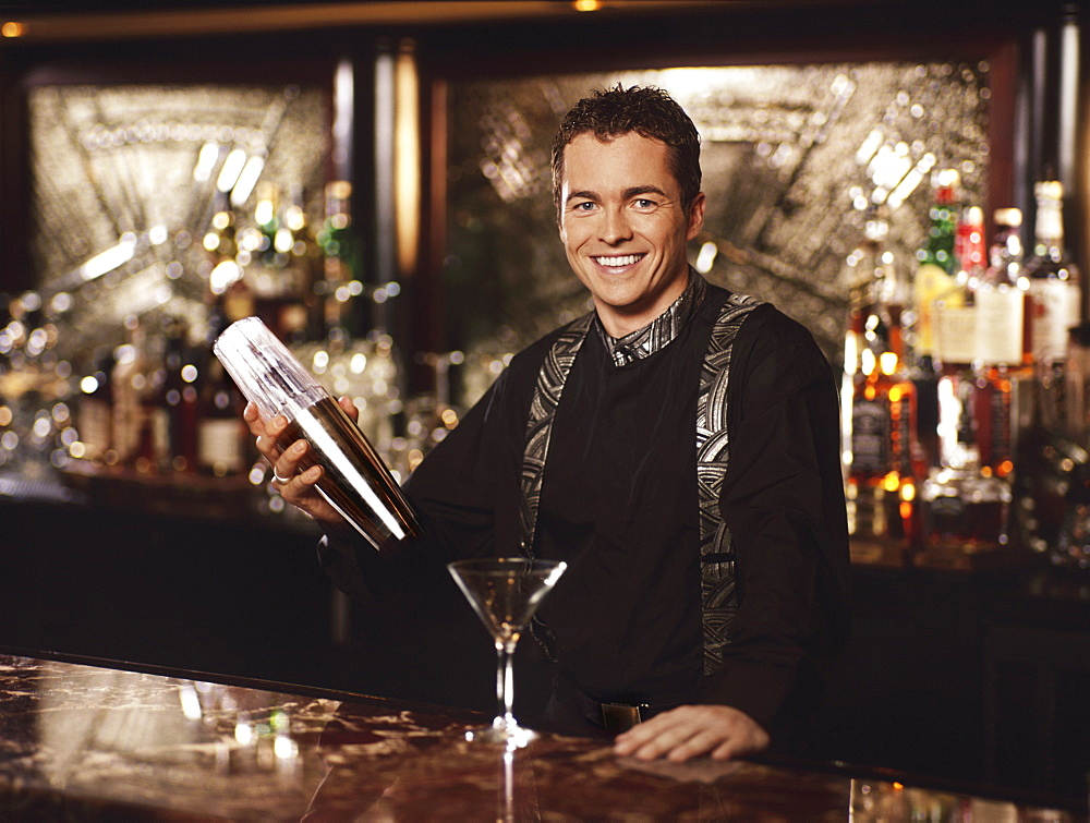 Young man standing behind bar shaking cocktail shaker, portrait