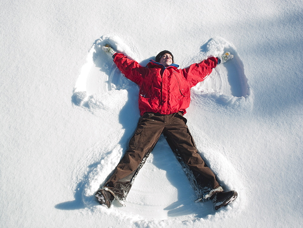 Woman making snow angel