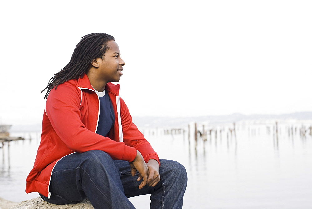 Teenage boy (16-17) with dreadlocks, sitting at waterfront, San Francisco, California, USA