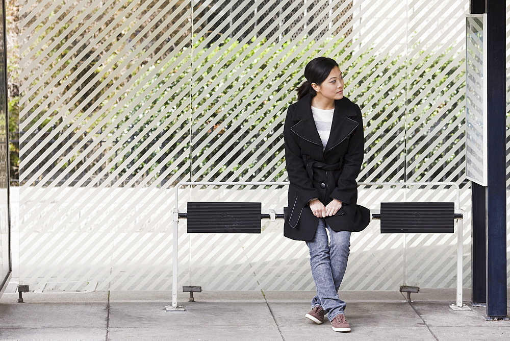 Young woman waiting at bus stop, San Francisco, California, USA