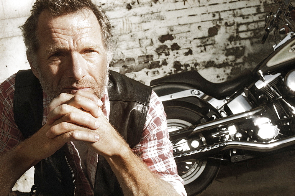 Mature man in front of motorcycle