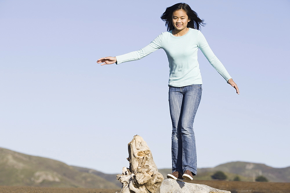 Teenage girl balancing on driftwood
