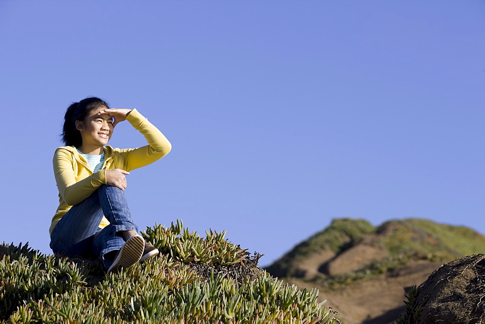 Teenage girl sitting on hill