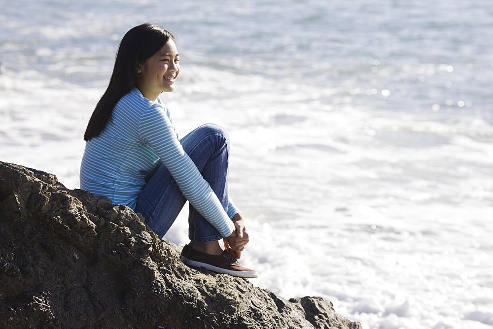 Teenage girl sitting on coastal rock