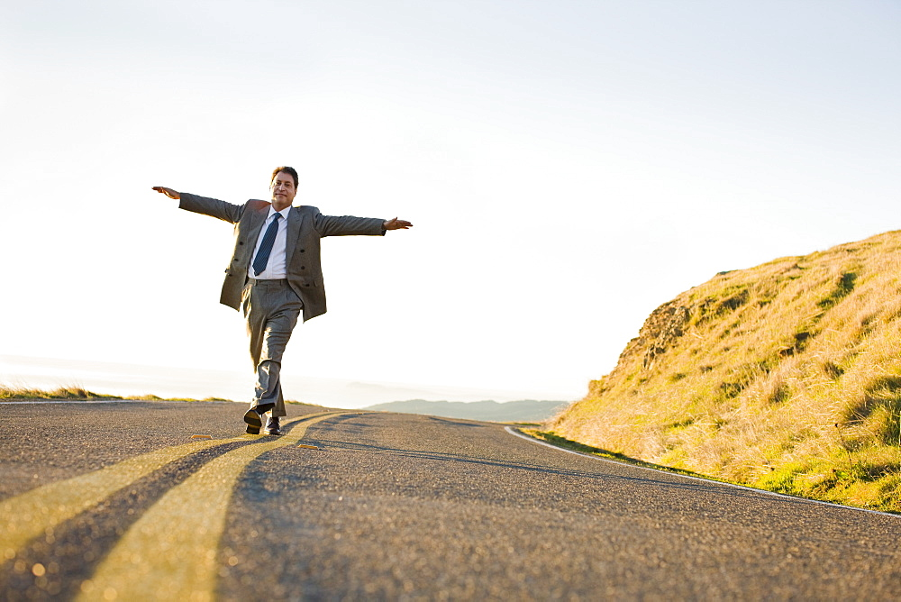 Businessman running on remote road
