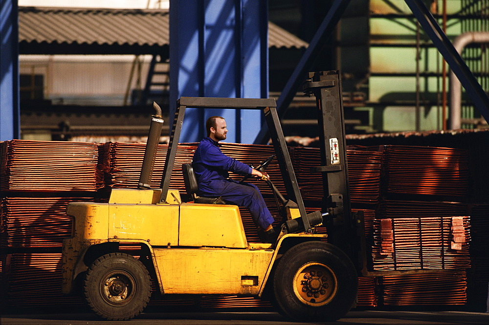 Worker lifting pallets of copper pipes on forklift
