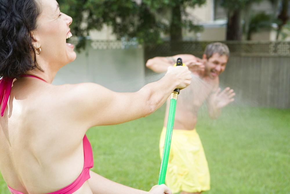 Woman spraying man with hose in backyard