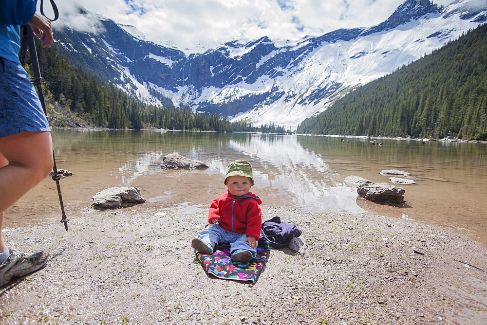 Boy (4-5) sitting on lakeshore, Avalanche Lake, Glacier National Park, Montana, USA