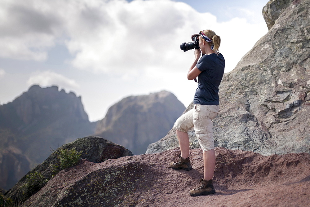 Woman photographing in mountains, Big Bend National Park, Texas, USA