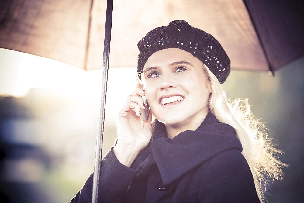Smiling woman under umbrella using mobile phone